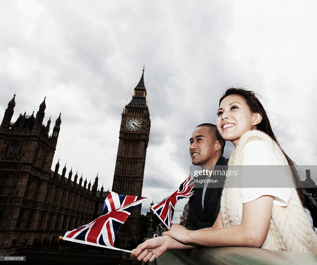 Smiling Asian tourist couple waving small Union Jacks in front of Houses of Parliament, London, England, UK : Stock Photo