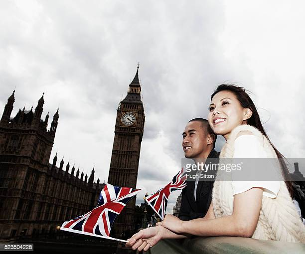 smiling asian tourist couple waving small union jacks in front of houses of parliament, london, england, uk - hugh sitton stock pictures, royalty-free photos & images