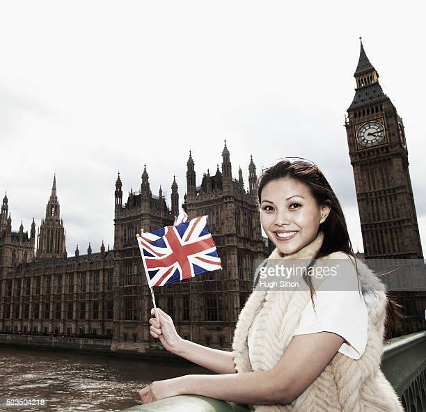 smiling asian tourist waving small union jack in front of houses of parliament, london, england, uk - hugh sitton stock pictures, royalty-free photos & images