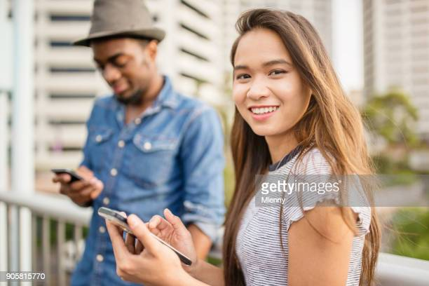 Smiling asian woman checking messages on smart phone