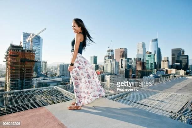 smiling asian woman standing on windy urban rooftop - windy skirt fotografías e imágenes de stock