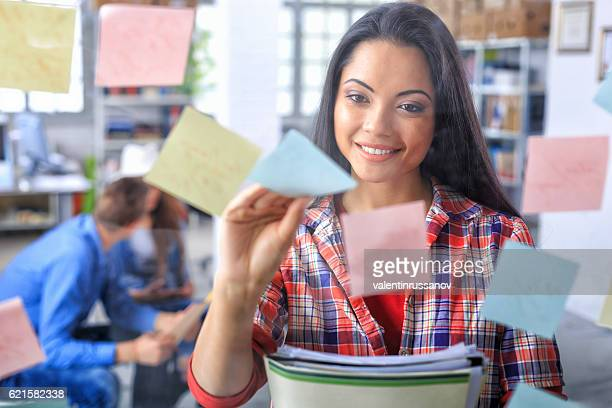 Smiling asian woman taking post-it notes from glass wall