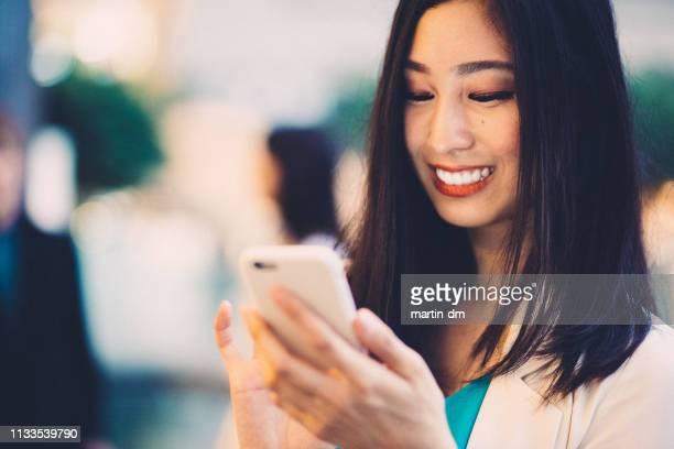 街の中で笑顔アジアの女性のテキスト - スマートフォン ストックフォトと画像