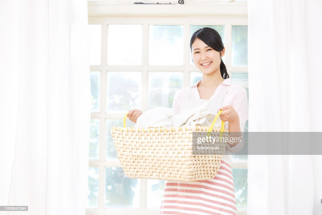 smiling Asian woman with the laundry : Stock Photo