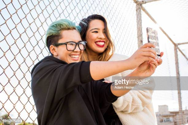 smiling asian women posing for cell phone selfie - androgynous stock pictures, royalty-free photos & images