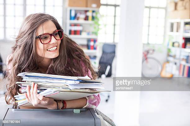 smiling assistant leaning on copy machine in workplace - part time job stock pictures, royalty-free photos & images