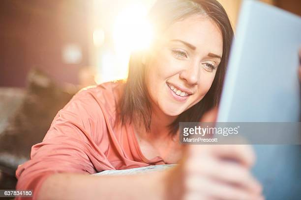 smiling at her digital tablet