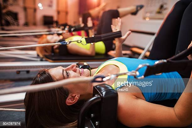 Smiling athlete exercising on Pilates machine during training class.