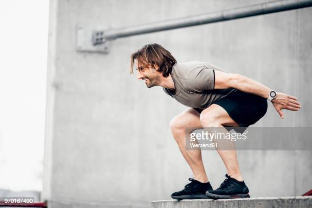 smiling athlete exercising outdoors - crouching stock pictures, royalty-free photos & images