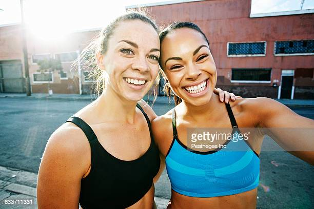 Smiling athletes hugging outdoors