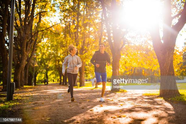glimlachend atleten lopen samen in het park. - joggen stockfoto's en -beelden