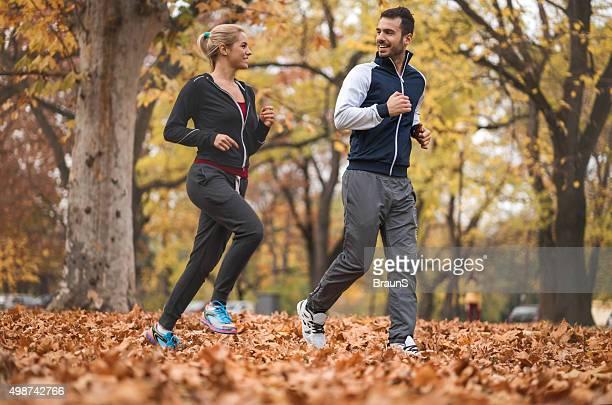 Souriant les athlètes à courir ensemble dans le parc et de la communication.
