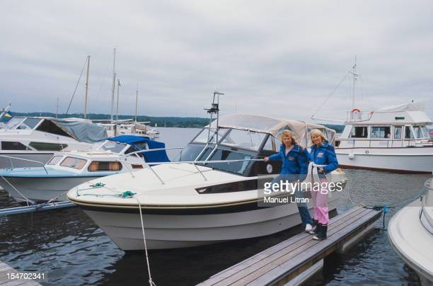 Smiling attitude of Bjorn Ulvaeus and Agnetha Faltskog his wife posing on a dock beside a boat anchor in port