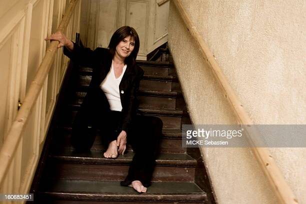 Smiling attitude of Catherine Breillat director of 'An old mistress' sitting barefoot on a staircase