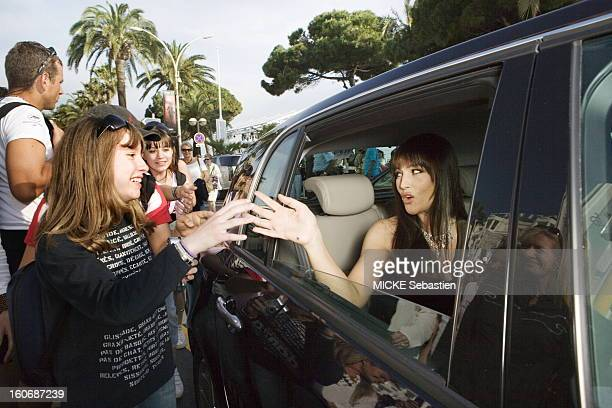 Smiling attitude of Monica Bellucci in the back seat of a car with the window is down shaking hands with a young fan
