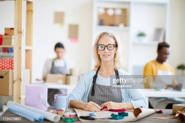 Smiling attractive mature lady in glasses wearing stripped apron sitting at table with ribbons and wrapping papers and looking at camera in gift workshop