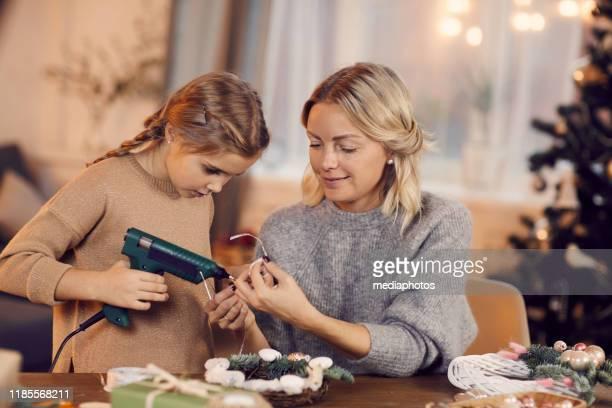 lächelnd attraktive junge mutter in pullover sitzt am tisch im wohnzimmer und hilft tochter, weihnachtskranz zu machen - heimwerken stock-fotos und bilder