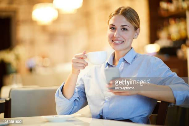 Smiling attractive young woman in shirt sitting at table and looking at camera while drinking coffee and reading message on phone
