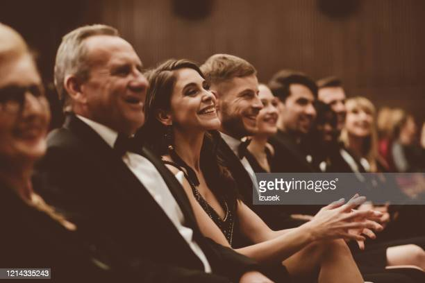 smiling audience sitting in the theater - awards ceremony stock pictures, royalty-free photos & images