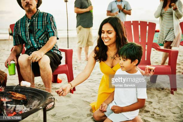 smiling aunt helping nephew roast marshmallows over fire during family beach party - aunt stock pictures, royalty-free photos & images