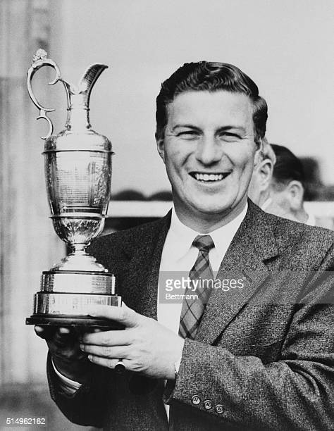 Smiling Australian golfer Peter Thomson proudly holds his trophy after winning the British Open golf championship with a 72 hole score of 281 to...