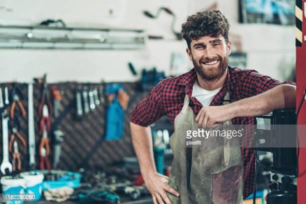 lächelnde auto-reparatur-garage-besitzer - handwerker stock-fotos und bilder