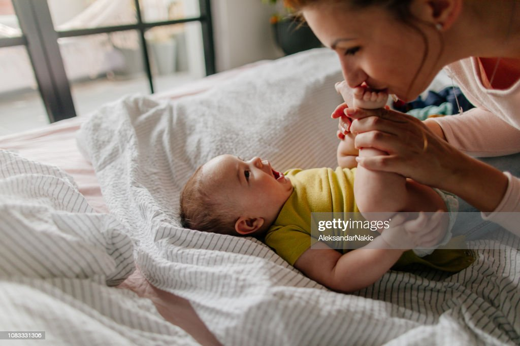 Smiling baby and his mom : Stock Photo