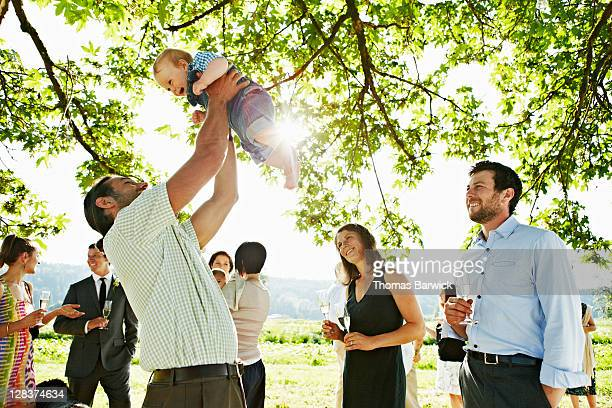 Smiling baby being lifted up in the air at party