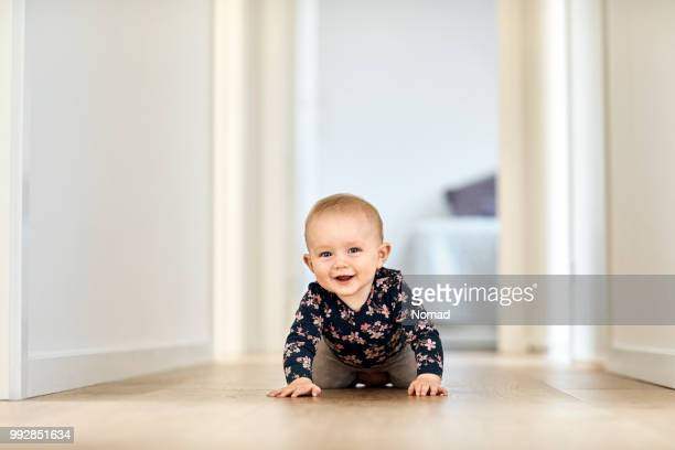 smiling baby boy crawling in corridor at home - babyhood stock pictures, royalty-free photos & images