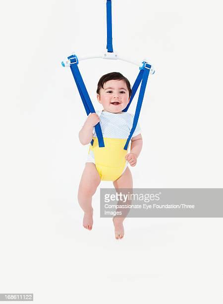 smiling baby boy in baby bouncer - バウンサー ストックフォトと画像