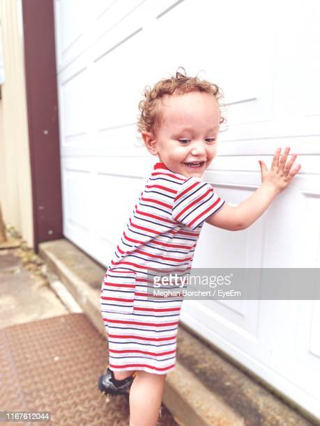smiling baby boy standing by white door - meghan stock photos and pictures