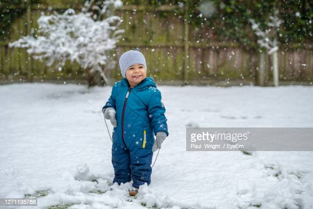 smiling baby boy standing in snow during winter - one baby boy only stock pictures, royalty-free photos & images