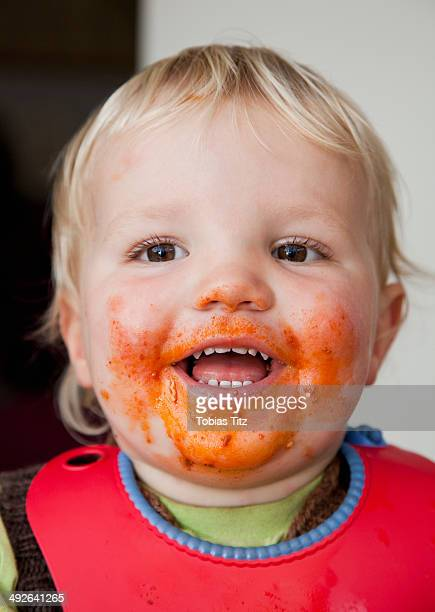 A smiling baby boy with food on his face close-up
