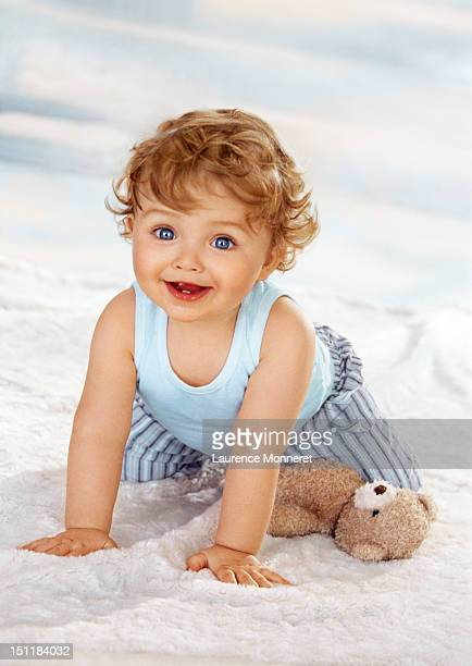 Smiling baby crawling on soft blanket on floor