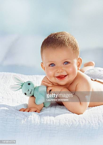 Smiling baby crawling with a blue rabbit toy