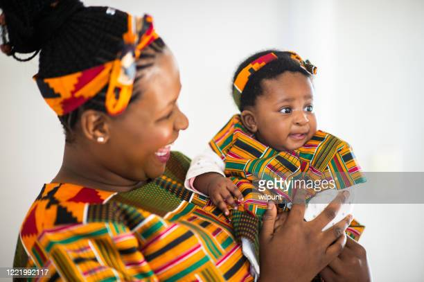 smiling baby daughter in traditional clothing with mother - zulu women stock pictures, royalty-free photos & images