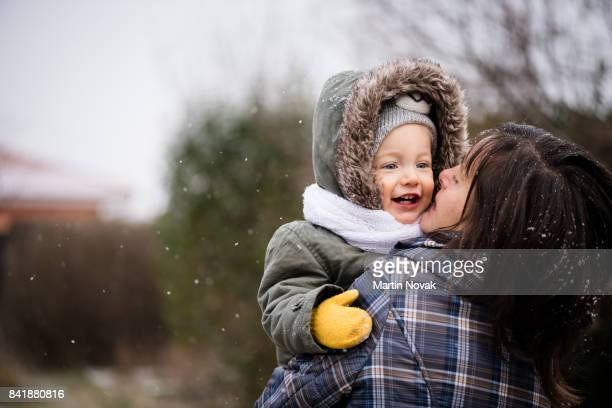 Smiling baby girl and mother in winter park