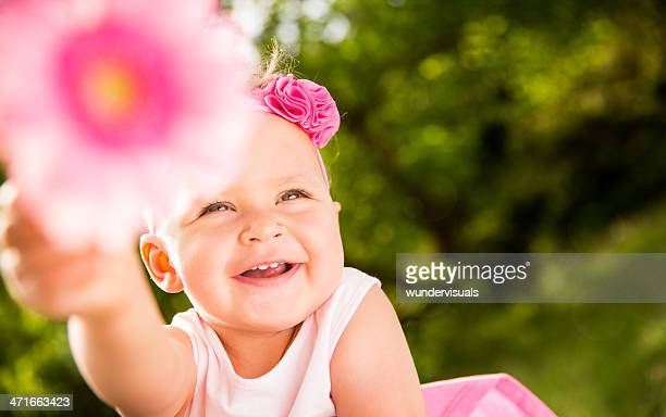 smiling baby girl pointing flower at camera - baby pointing stock photos and pictures