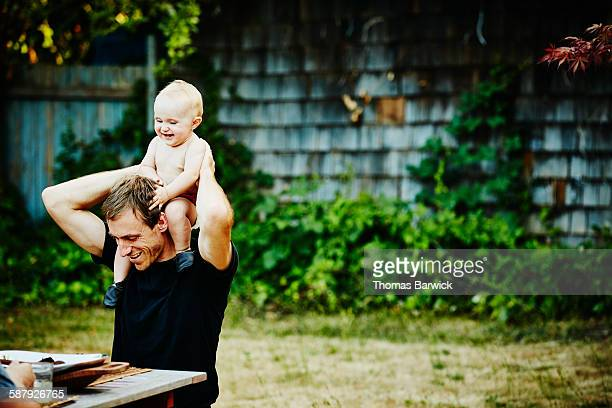 Smiling baby girl sitting on fathers shoulders