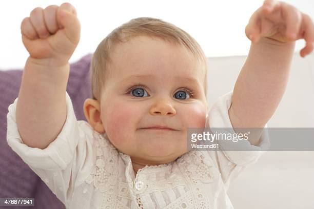 Smiling baby girl with outstrechted arms