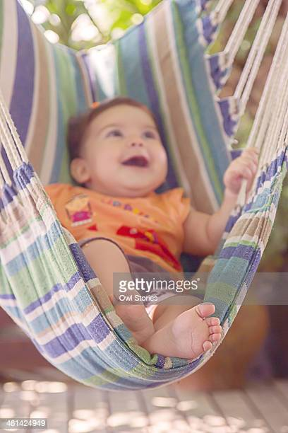 Smiling baby having fun on a fabric outdoor swing