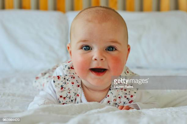 smiling baby lying on her stomach - rosy cheeks stock pictures, royalty-free photos & images