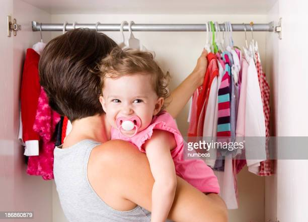 Smiling baby on the shoulders of woman looking at closet