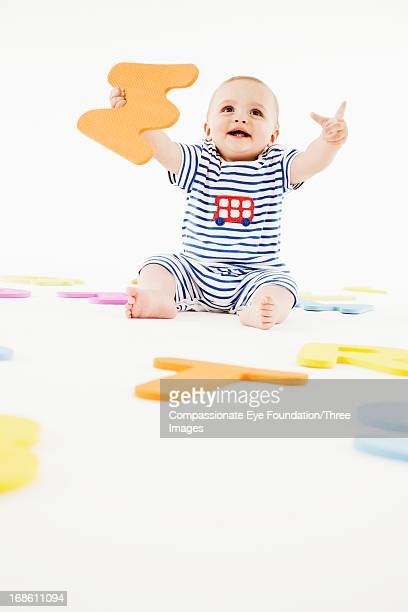 Smiling baby playing with toy letters