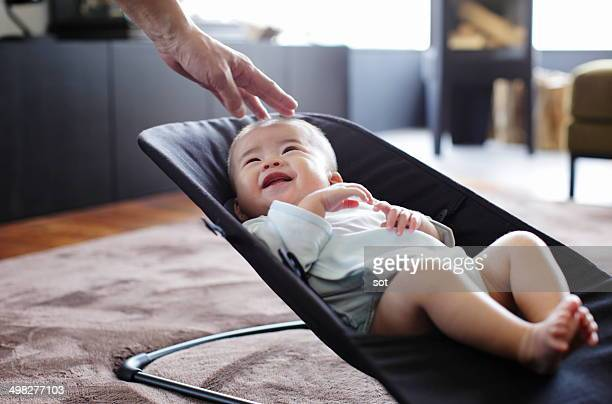 Smiling baby with father's hand in bassinet