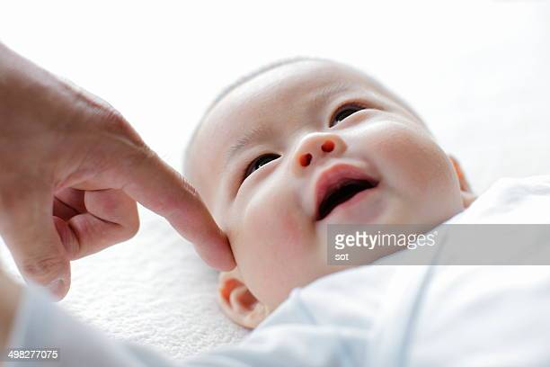 Smiling baby with finger of father,close up