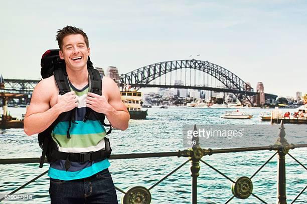 Smiling backpacker in front of harbor bridge