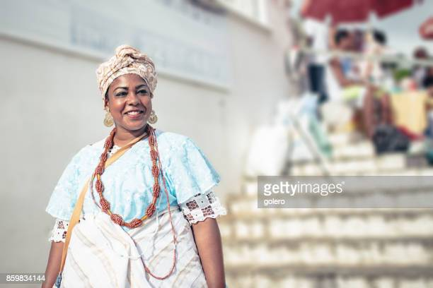 smiling baiana in traditional colorful costume in front of church in Salvador