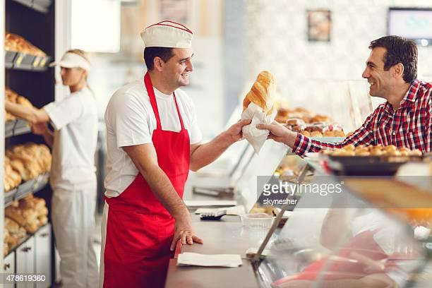 笑顔のベイカーとその顧客のベーカリー」。