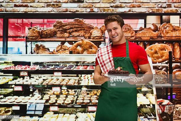 Smiling baker holding dish